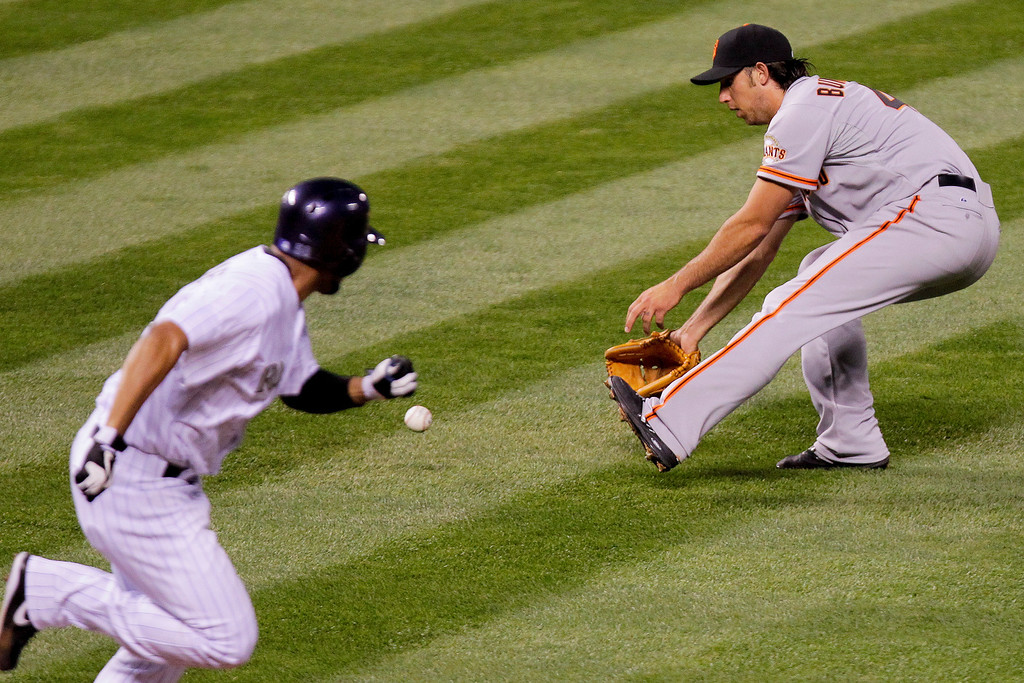 . Colorado Rockies\' Franklin Morales, left, successfully bunts on a pitch from San Francisco Giants starting pitcher Madison Bumgarner, right, during the fourth inning of a baseball game, Tuesday, April 22, 2014, in Denver. Giants first baseman Brandon Belt was given an error on the play. (AP Photo/Barry Gutierrez)