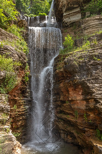 Multi-tiered waterfall over stone canyon wall