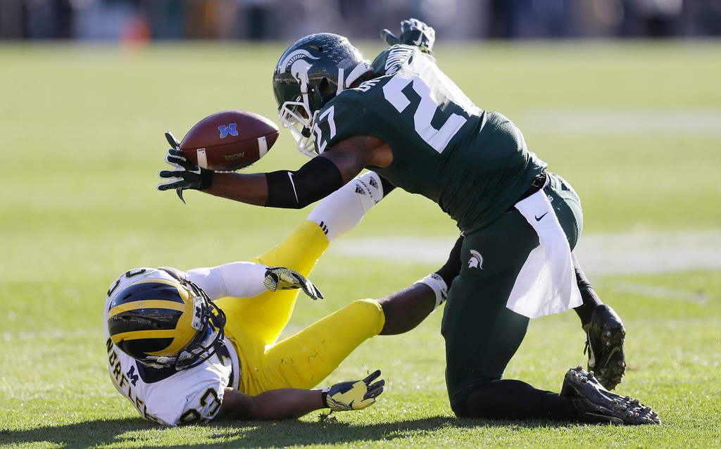 . Michigan State safety Kurtis Drummond (27) reacts after tackling Michigan wide receiver Dennis Norfleet (23) during the first half of an NCAA college football game in East Lansing, Mich., Saturday, Oct. 25, 2014. (AP Photo/Carlos Osorio)