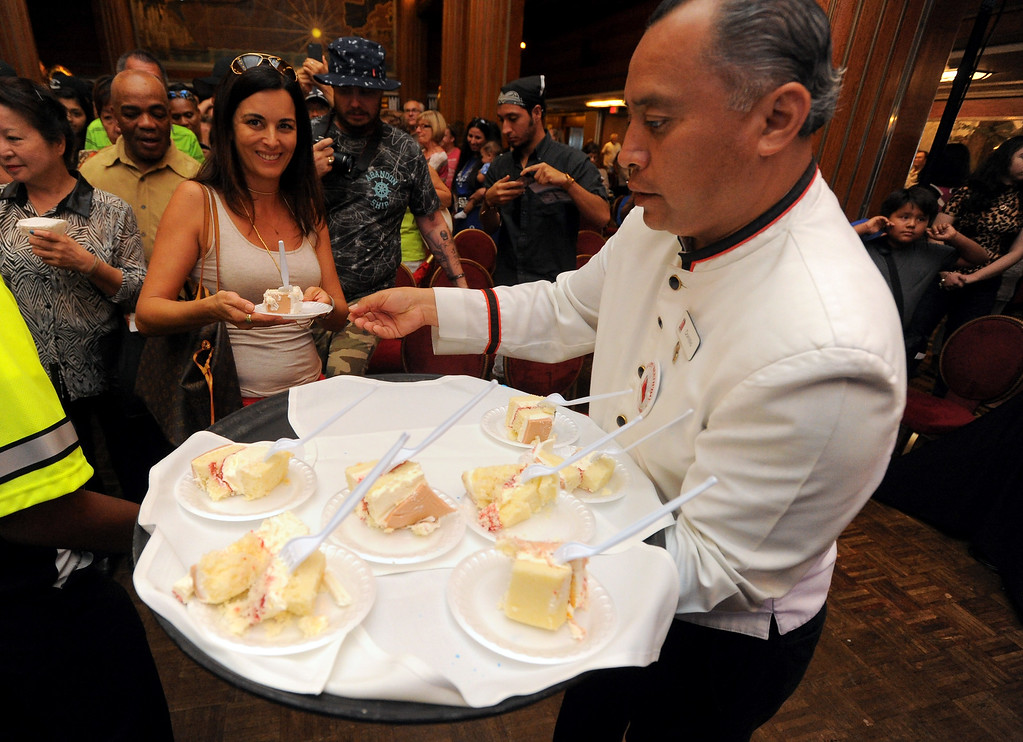 . Cake is handed out to visitors as the Queen Mary celebrated its 80th anniversary of her launching by inviting the public to tour the ship for free in Long Beach, CA on Friday, September 26, 2014. After some speeches and a short film, guests were able to sample a slice of cake from a 15-foot long, 600-pound replica of the ship made by baker Jose Barajas. (Photo by Scott Varley, Daily Breeze)