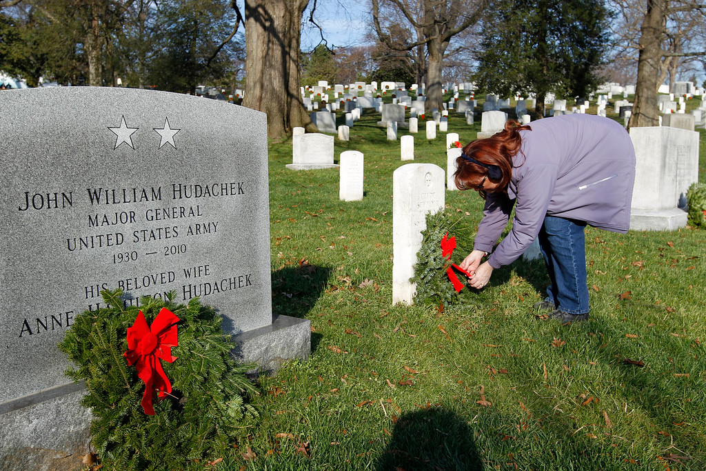 . Volunteer Carol Vassallo lays holiday wreaths at the graves of fallen soldiers at Arlington National Cemetery in Washington Saturday Dec. 10, 2011, during Wreaths Across America Day. (AP Photo/Jose Luis Magana)