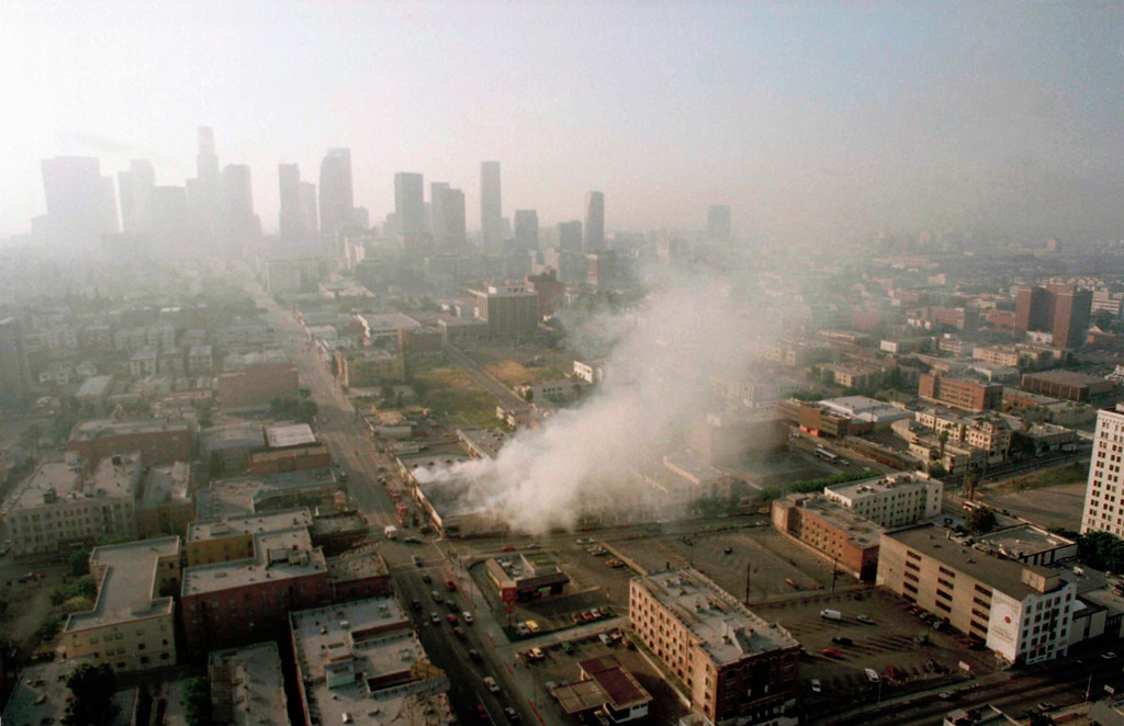 . Smoke rises from a shopping center burned by rioters early Thursday morning April 30, 1992 as the Los Angeles skyline is partially obscured by smoke. More than 300 fires were reportedly set after four police officers were acquitted Wednesday of the beating of motorist Rodney King. (AP Photo/Paul Sakuma)
