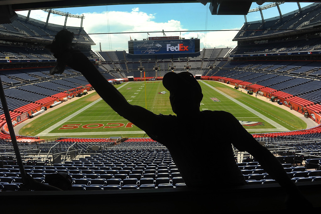 . Aramark employees James Voyce, center, and Nick Gurule, left,  thoroughly clean the windows in all the luxury suites on the second level of Sports Authority Field at Mile High in Denver on Tuesday September 4, 2013. They, and hundreds of others, were preparing the stadium to make it look it\'s best for the NFL season opener when the Denver Broncos take on the Baltimore Ravens Thursday night.  Photo by Helen H. Richardson/The Denver Post