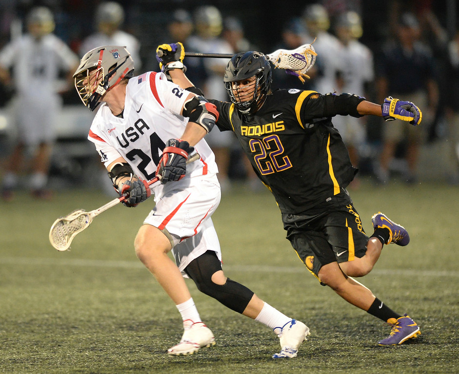 . United States midfielder Chris Eck (24) made off with the ball after winning a face-off against Iroquois midfielder Jerome Thompson (22) in the second half. The United States defeated the Iroquois Nationals 18-5 Tuesday night, July 15, 2014.   Photo by Karl Gehring/The Denver Post