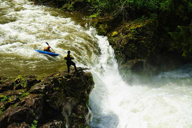 "Christian Woodard runs ""Big Kahuna"" at high water on Portland's local Canyon Creek as Casey Sande looks on."