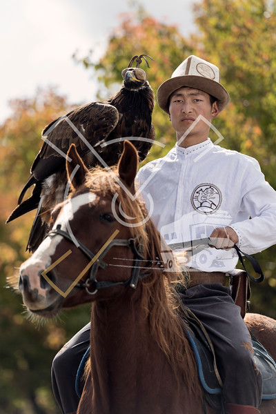 Kyrgyz young man on a horse posing with his hunting eagle outdoors in Kyrgyzstan.