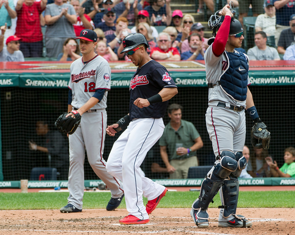 . Cleveland Indians\' Michael Brantley scores on a single by Edwin Encarnacion as Minnesota Twins starting pitcher Jake Odorizzi (12) and catcher Mitch Garver stand by during the fourth inning of a a baseball game in Cleveland, Thursday, Aug. 30, 2018. (AP Photo/Phil Long)
