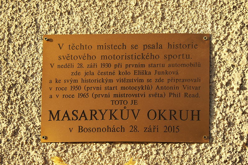 """The plaque says: """"On this very spot, motorsport history was being written. On Sunday 28th September 1930, Eliška Junková has done a honorary lap of the track as part of the very first automobile race at this track, and Antonin Vitvar in 1950 (first motorbike race on the track) and Phil Read in 1965 (first world championship) prepared here for their legendary wins. This is Masaryk Circuit. In Bosonohy, 28th September 2015."""""""