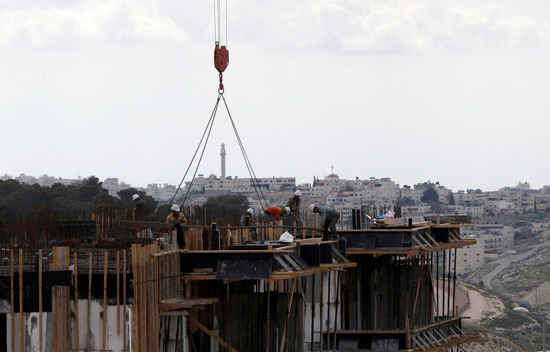 . The West Bank town of Bethlehem is seen in the background as Palestinian laborers work on a construction site at a Jewish settlement near Jerusalem known to Israelis as Har Homa and to Palestinians as Jabal Abu Ghneim on March 18, 2013. Israel\'s new housing minister said on Sunday that Prime Minister Benjamin Netanyahu\'s incoming cabinet would keep expanding Jewish settlements to the same extent as his previous government.  REUTERS/Baz Ratner