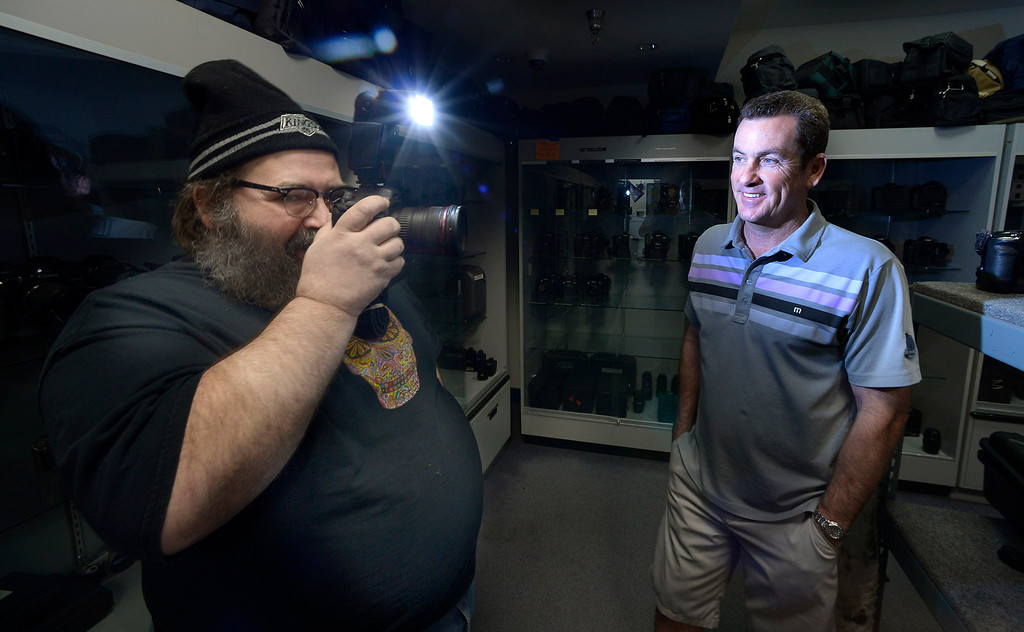 . Robert Phippen uses a rubber prop camera with a working flash to illuminate Gregg Bilson, Jr. Bilson is the CEO of ISS Independent Studio Services, a prop house that holds hundreds of thousands of items used for motion pictures and television production. Runaway production has an impact on his business. Sunland, CA 12-31-2013. photo by (John McCoy/Los Angeles Daily News)