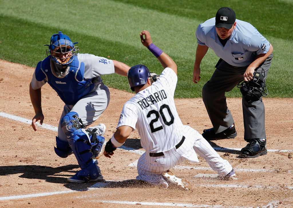 . DENVER, CO - SEPTEMBER 17:  Catcher Tim Federowicz #26 of the Los Angeles Dodgers tags out Wilin Rosario #20 of the Colorado Rockies as homeplate umpire Dan Bellino oversees the action in the first inning at Coors Field on September 17, 2014 in Denver, Colorado.  (Photo by Doug Pensinger/Getty Images)