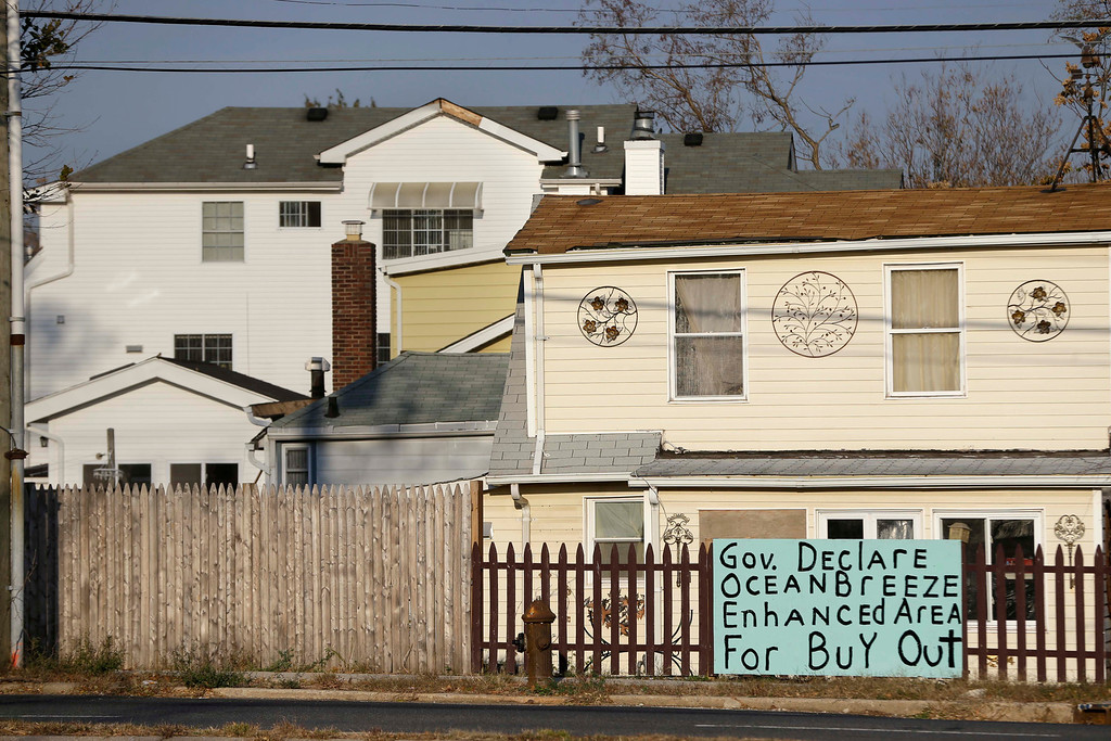 ". Signs asking for a ""buy out\"" hang in front of homes damaged by Superstorm Sandy in the Ocean Breeze section of Staten Island, New York, Tuesday, Oct. 29, 2013.  (AP Photo/Seth Wenig)"