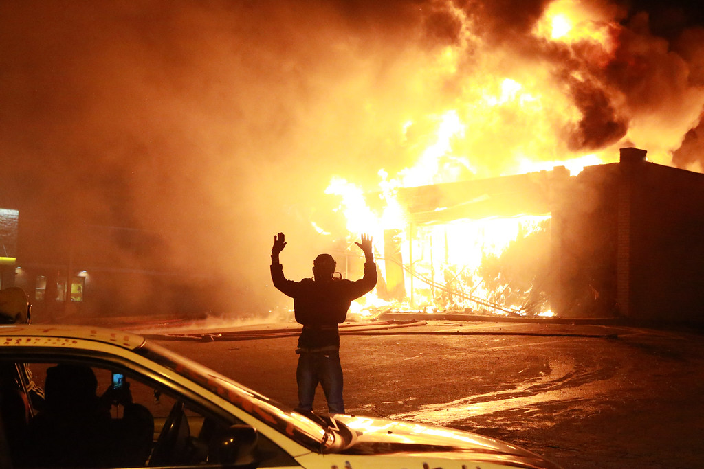 ". A protestor poses for a ""hands up\"" photo in front of a burning building on West Florissant Ave. in Ferguson, Mo., Monday, Nov. 24, 2104. Chaos returned to the streets of Ferguson after a grand jury declined to indict white police officer Darren Wilson in the death of Michael Brown. (AP Photo/St. Louis Post-Dispatch, Christian Gooden)"