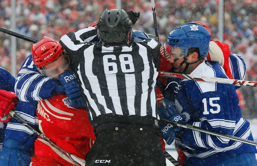 . Linesman Scott Driscoll (68) separates Detroit Red Wings right wing Luke Glendening, left, and Toronto Maple Leafs defenseman Paul Ranger (15) during a scuffle in the second period of the Winter Classic outdoor NHL hockey game at Michigan Stadium in Ann Arbor, Mich., Wednesday, Jan. 1, 2014. (AP Photo/Paul Sancya)