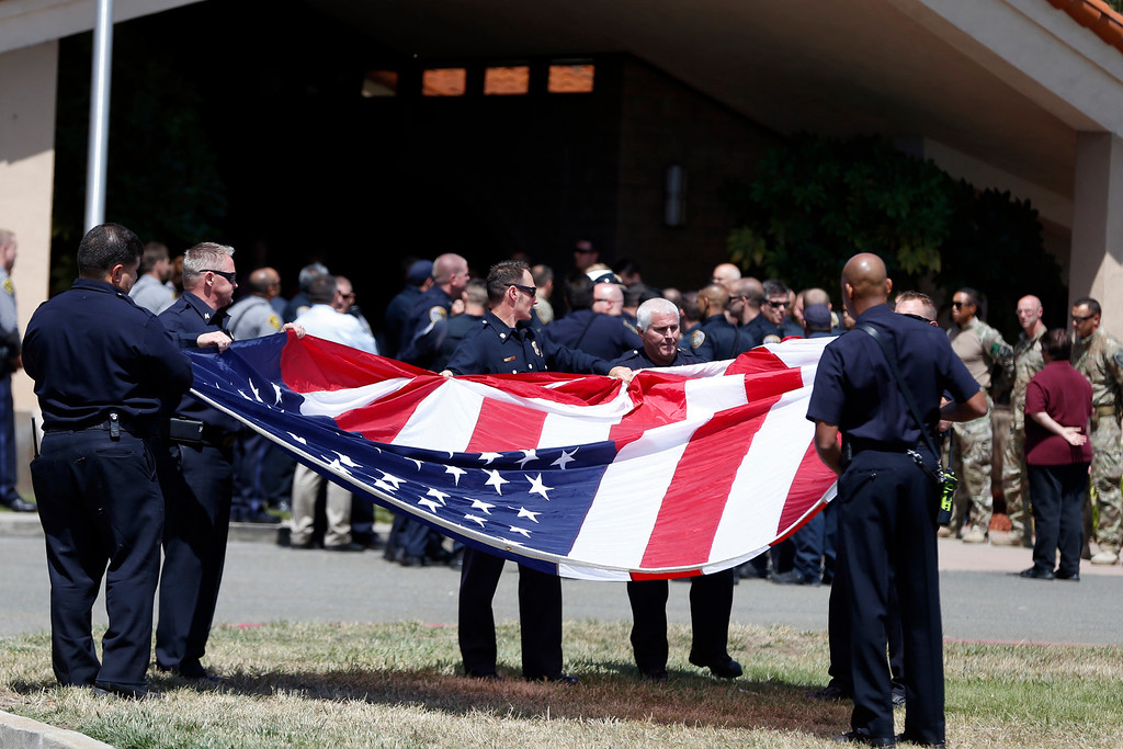. Hayward firefighters fold an American flag at the conclusion of the procession with the body of Hayward police Sgt. Scott Lunger from the Coroner\'s Bureau in Oakland to Chapel of the Chimes Memorial Park in Hayward, Calif., on Thursday, July 23, 2015. Lunger was killed during a traffic stop in early Wednesday. (Ray Chavez/Bay Area News Group)