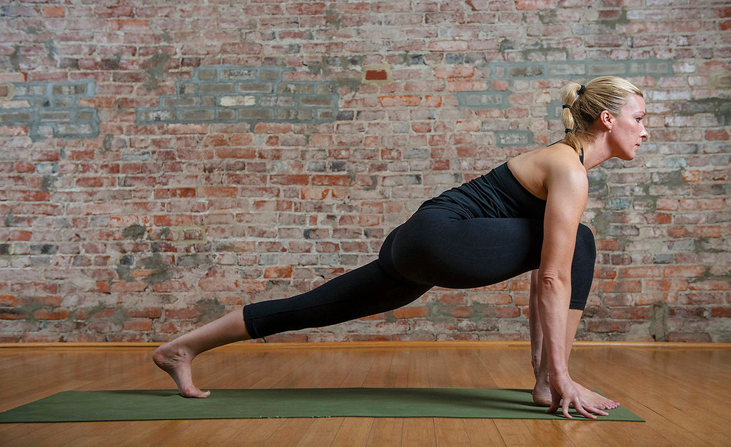 . Sun salutation, left to right: 5) On the next exhale, step one foot back into a lunge, then both feet into plank pose, which looks like the top of a push-up.  (Photo for The Washington Post by Amanda Voisard.)