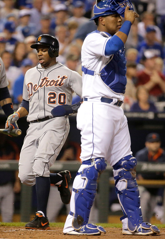 . Detroit Tigers\' Rajai Davis runs past Kansas City Royals catcher Salvador Perez to score on a double by Torii Hunter during the second inning of a baseball game Friday, Sept. 19, 2014, in Kansas City, Mo. (AP Photo/Charlie Riedel)