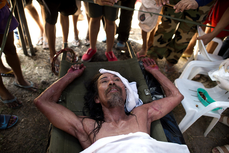 . A Philippine Christian devotee rests on a stretcher as he receives medical treatment after being nailed to a cross during the a re-enactment of the Crucifixion of Christ during Good Friday celebrations ahead of Easter in the village of Cutud, Pampanga, north of Manila on April 18, 2014.  Eight Filipinos and a Dane re-enacted the death of Jesus Christ on Friday by nailing themselves to crosses before thousands of people in a gruesome annual Easter spectacle in the Philippines. The crucifixion ritual -- held every year to mark Good Friday in Asia\'s bastion of Catholicism -- has been going on for decades, becoming a major tourist draw despite official disapproval from Church leaders.  (NOEL CELIS/AFP/Getty Images)