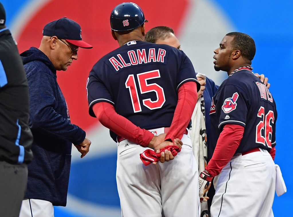 . Cleveland Indians\' Rajai Davis is checked by a trainer during the second inning of the team\'s baseball game against the Toronto Blue Jays, Friday, April 13, 2018, in Cleveland. (AP Photo/David Dermer)