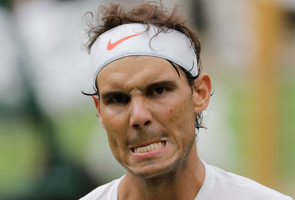 . Rafael Nadal of Spain grimaces after winning a point during the men\'s singles semifinals match against Serbia\'s Novak Djokovic at the Wimbledon Tennis Championships, in London, Saturday July 14, 2018.(AP Photo/Ben Curtis)