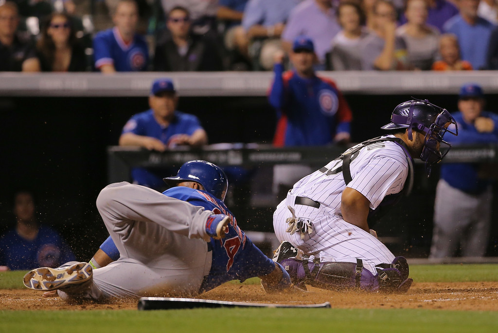 . DENVER, CO - AUGUST 05:  Luis Valbuena #24 of the Chicago Cubs slides home to score past catcher Wilin Rosario #20 of the Colorado Rockies on a sacrifice fly by Chris Valaika #4 of the Chicago Cubs to give the Cubs a 4-3 lead in the seventh inning at Coors Field on August 5, 2014 in Denver, Colorado.  (Photo by Doug Pensinger/Getty Images)