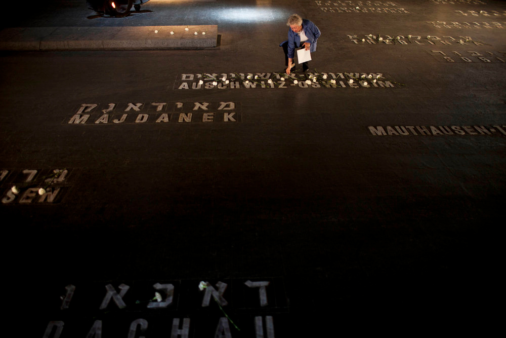 Description of . A relative of Holocaust victims lays flowers next to names of concentration camps during a ceremony marking the annual Holocaust Remembrance Day at the Yad Vashem Holocaust Memorial in Jerusalem on Monday, April 8, 2013. Israel came to a standstill for two mournful minutes Monday as sirens pierced the air in an annual ritual to remember the 6 million Jews systematically murdered by German Nazis and their collaborators during the Holocaust in World War II. (AP Photo/Oded Balilty)