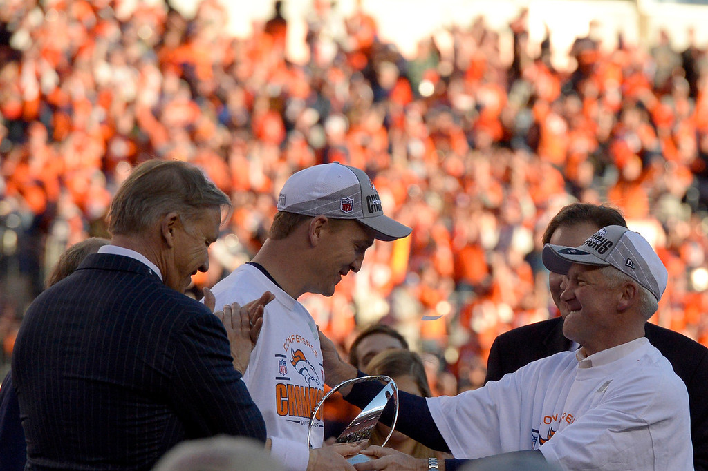 . Denver Broncos quarterback Peyton Manning (18) and head coach John Fox with Executive Vice President of football operations John Elway during the AFC Championship trophy presentation. The Denver Broncos beat the New England Patriots 26-16. The Denver Broncos vs. The New England Patriots in an AFC Championship game  at Sports Authority Field at Mile High in Denver on January 19, 2014. (Photo by Joe Amon/The Denver Post)