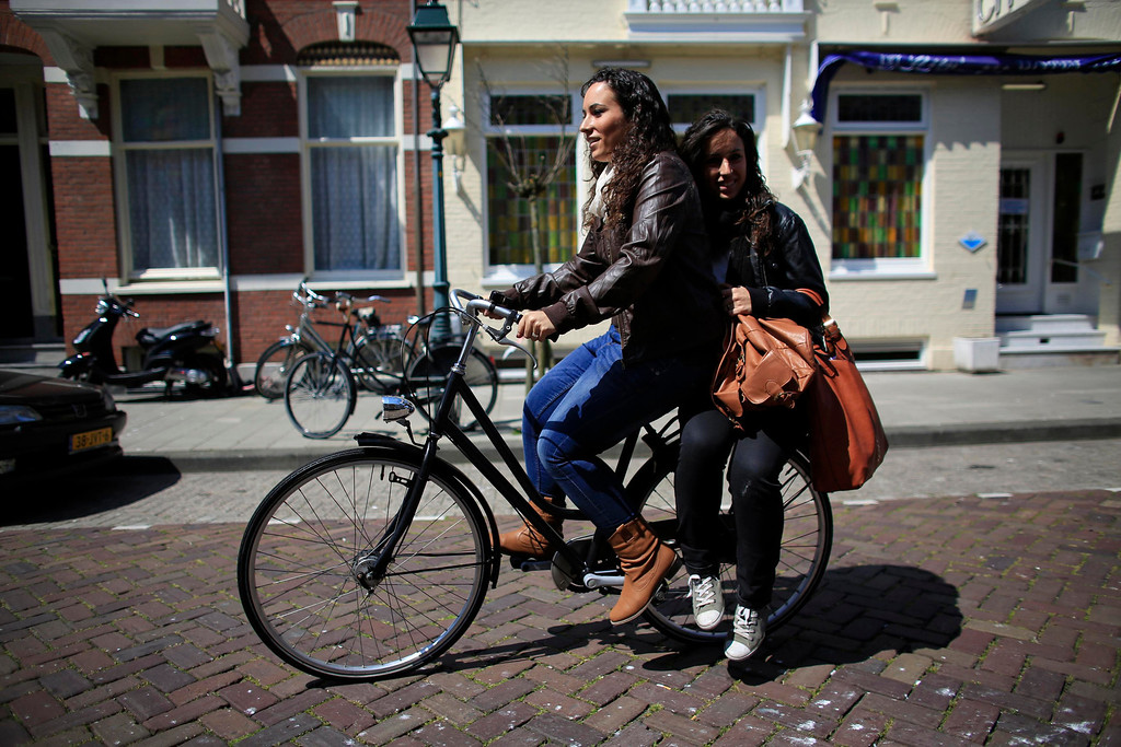 . Spanish nurse Maria Teresa Marin (L), 23, rides a bicycle with her twin sister Maria Jose on the back, in The Hague, June 7, 2013. After months of studying Dutch, a group of young Spanish nurses moved to the Netherlands to take up work, fleeing a dismal job market at home. Spain\'s population dropped last year for the first time on record as young professionals and immigrants who moved here during a construction boom head for greener pastures. Spain\'s jobless rate is 27 percent, and more than half of young workers are unemployed. For Spanish nurses, the Netherlands\' nursing deficit is a boon. Picture taken June 7, 2013.  REUTERS/Marcelo del Pozo