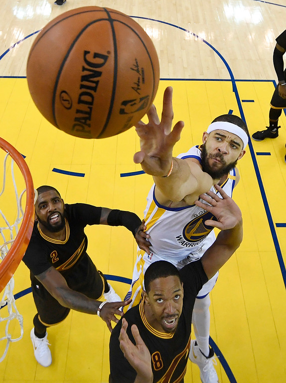 . Golden State Warriors center JaVale McGee, top, reaches for the ball over Cleveland Cavaliers guard Kyrie Irving (2) and forward Channing Frye (8) during the first half of Game 2 of basketball\'s NBA Finals in Oakland, Calif., Sunday, June 4, 2017. (Kyle Terada/Pool Photo via AP)