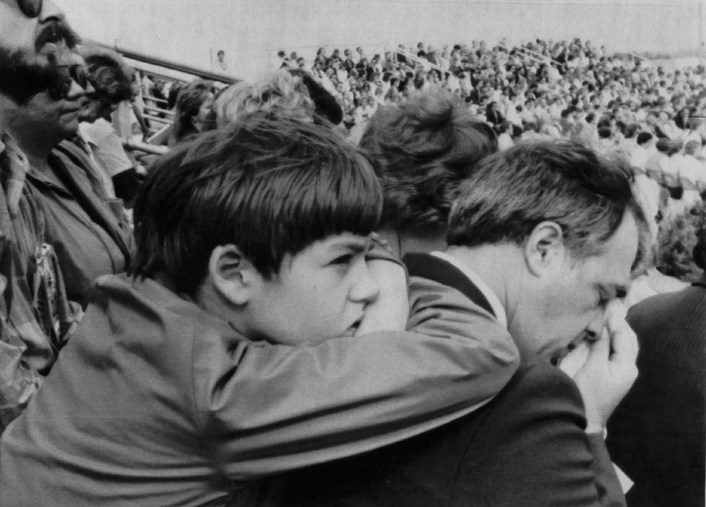 Description of . An unidentified worker at the Kennedy Space Center wipes a tear from his eye as a youngster leans on his back during the memorial services on Feb.2, 1986 for the 7 astronauts that were killed when the space shuttle Challenger exploded 72 seconds after blasting off from here.  Denver Post Library Archive
