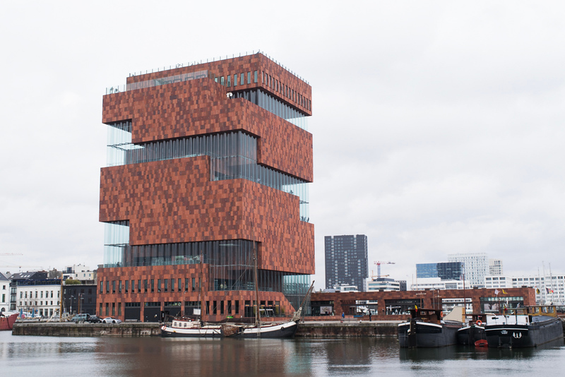 large building clad in brick and glass on a waterfront
