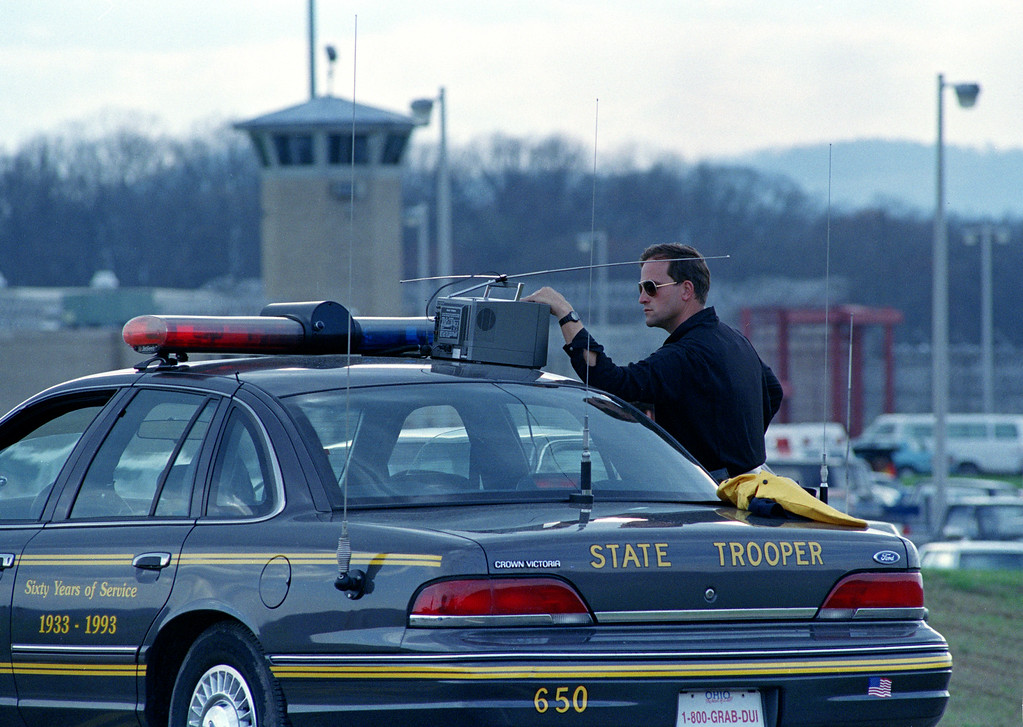 . An Ohio State Patrol trooper watches a television as he stands at his post at the roadway in front of the Southern Ohio Correctional Facility in Lucasville, Ohio, April 15, 1993. One of eight guards held hostage by prisoners was released after another was found dead. (AP Photo/Mark Duncan)