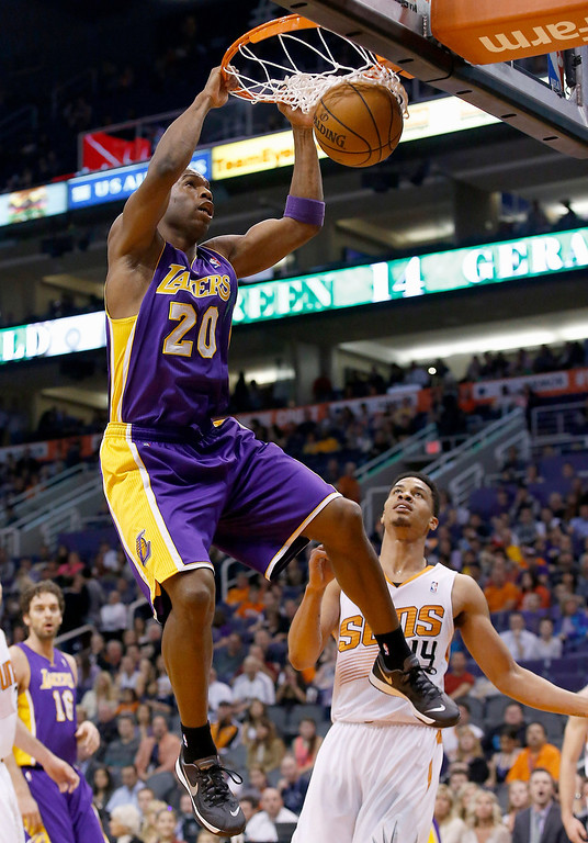 . Los Angeles Lakers\' Jodie Meeks (20) dunks as he gets past Phoenix Suns\' Gerald Green, right, during the first half of an NBA basketball game Wednesday, Jan. 15, 2014, in Phoenix. (AP Photo/Ross D. Franklin)