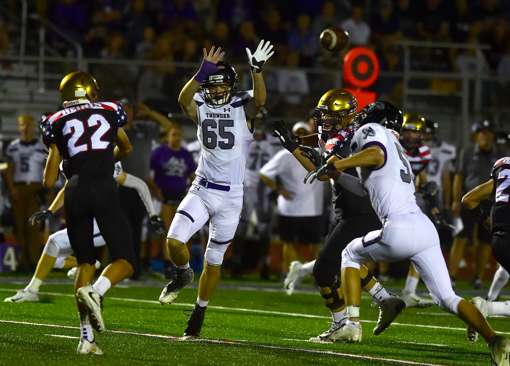 . BROOMFIELD CO - SEPTEMBER 14 2018 Holy Family High School\'s Calahan Carter makes a pass over Discovery Canyon High\'s Eli Scott during their game in Broomfield on Friday September 14, 2018. More photos bocopreps.com  (Photo by Paul Aiken/Staff Photographer)