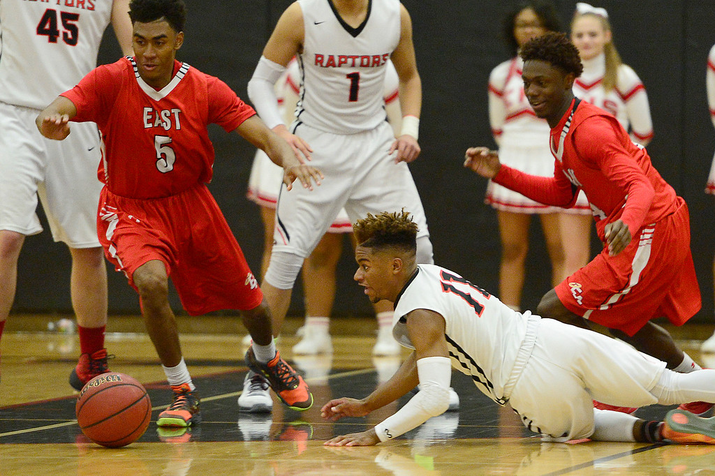 . CENTENNIAL, CO - MARCH 2: Elijah Wilson (11) of Eaglecrest dives after a loose ball while Deron Harrell (5) of Denver East tries to go after it during the fourth quarter at Eaglecrest High School on March 2, 2016 in Centennial, Colorado. Eaglecrest defeated Denver East 56-46. (Photo by Brent Lewis/The Denver Post)
