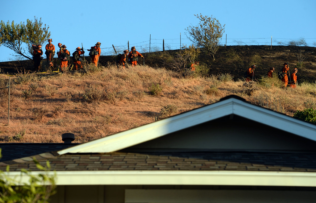 . Firefighters from the prison mop up following a vegetation fire above homes along Grimsby Drive in Antioch, Calif., on Wednesday, June 24, 2015. (Susan Tripp Pollard/Bay Area News Group)