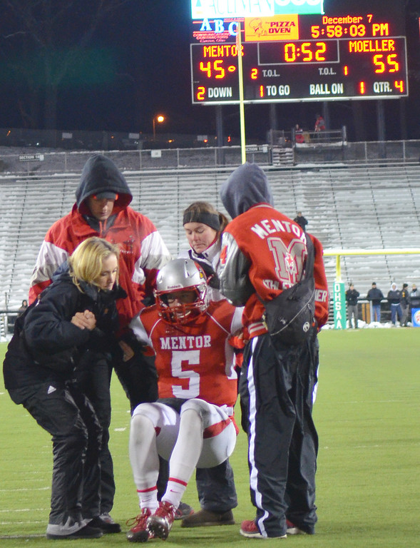 . Michael Allen Blair/ MBlair@News-Herald.com Mentor quarterback Conner Krizancic is helped off the field after getting hit hard inside the redzone during the final Mentor drive of Saturday\'s 55-52 Div. I state championship game loss to Cincinnati Moeller at Fawcett Stadium in Canton.