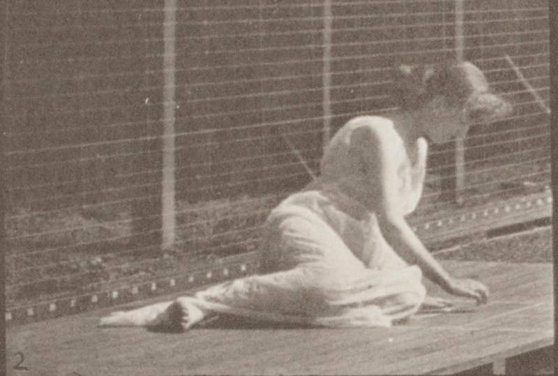 Semi-nude woman turning and changing position while on ground