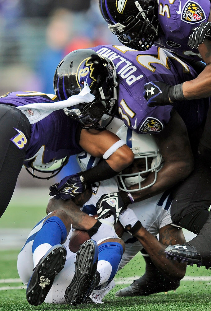 . Indianapolis Colts wide receiver Reggie Wayne (87) is tackled by Baltimore Ravens cornerback Cary Williams, left, strong safety Bernard Pollard, and inside linebacker Ray Lewis, top, during the first half of an NFL wild card playoff football game Sunday, Jan. 6, 2013, in Baltimore. (AP Photo/Nick Wass)