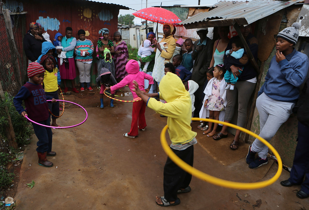 ". Children play hula-hoop after gifts were distributed by a charity on Christmas morning to residents in the Joe Slovo squatter settlement near Johannesburg, Sunday Dec. 25, 2016.  The gifts are donated by  the ""Children of Fire\"" charity which primarily aims to assists burn victims from across Africa. (AP Photo/Denis Farrell)"