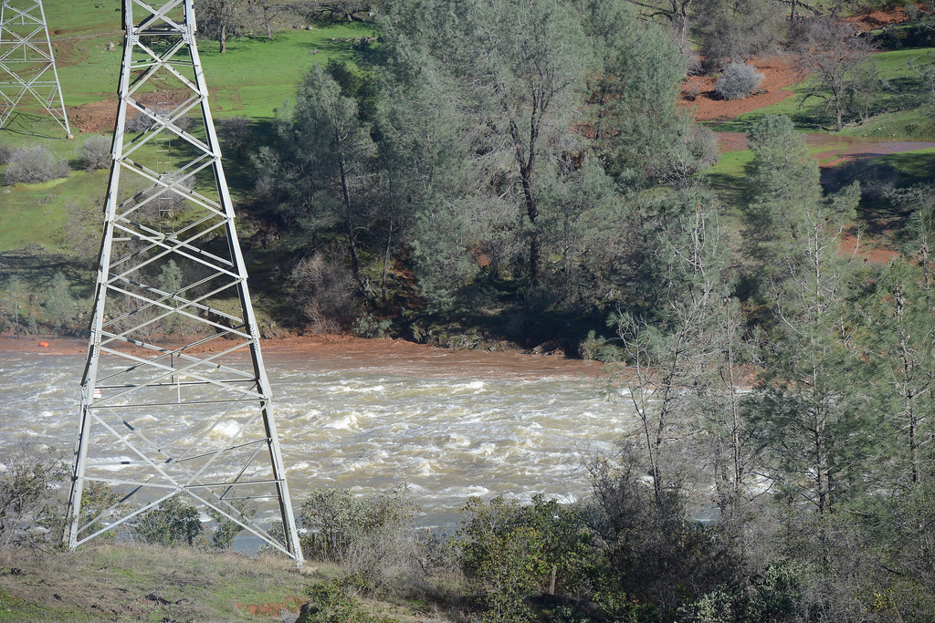 . Water from emergency spillway flows into the Diversion Pool at the center of this picture Saturday, Feb. 11, 2017, and in the main spillway in Oroville, California. Also pictured are two PG&E transmission towers. (Dan Reidel -- Enterprise-Record)