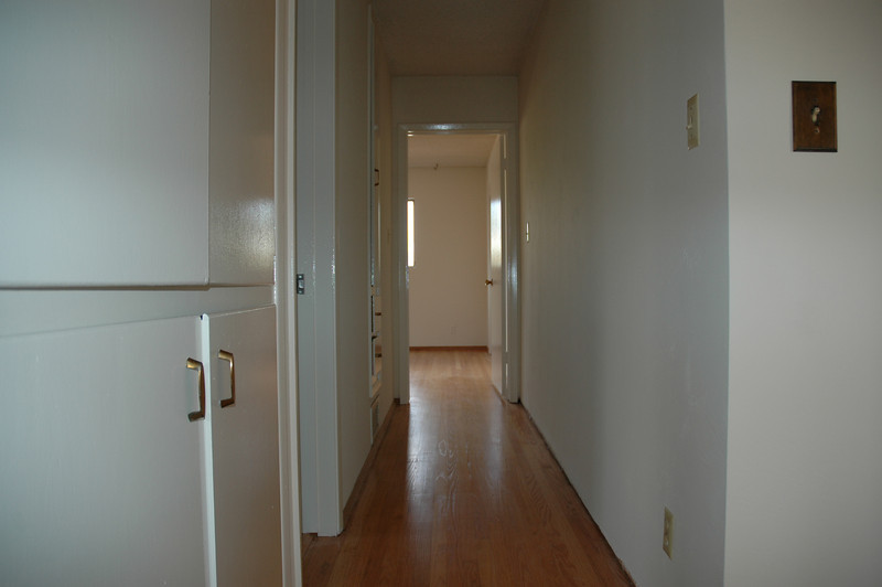 The hallway leading to the master bedroom. The hall bath is off to the left. Note the beautiful shine in the hardwood flooring.