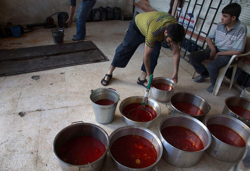 . A member of the Free Syrian army arranges pots of food to be delivered to the Free Syrian army fighters fighting at the front line in Deir al-Zor April 17, 2013. Picture taken April 17, 2013. REUTERS/ Khalil Ashawi