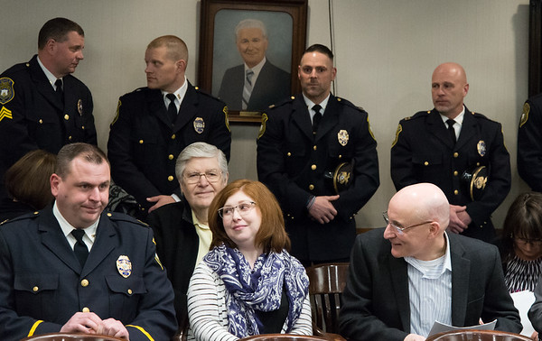 03/27/19 Wesley Bunnell | Staff Acting Police Chief Christopher Chute, seated L, speaks with former Police Chief James Wardwell, seated R, as several members of the department stand behind them in support of Chute.