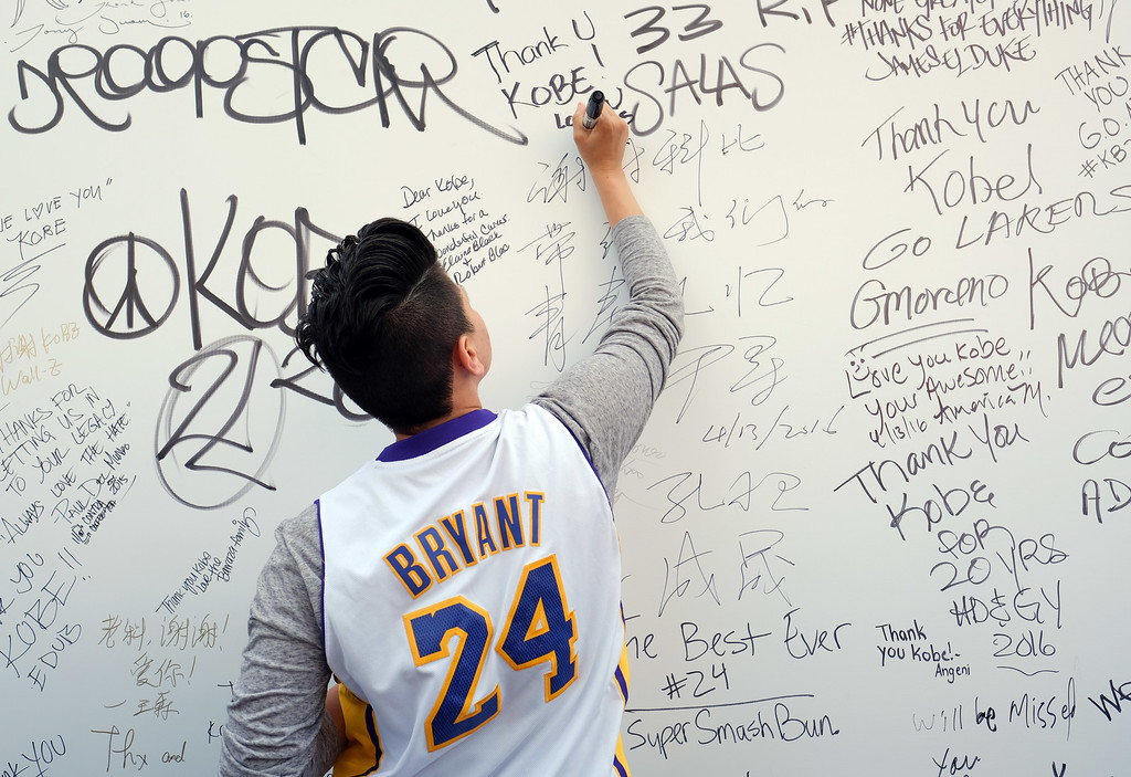 . A fan signs a large banner congratulating Kobe Bryant before his last NBA basketball game, a contest against the Utah Jazz, outside Staples Center in downtown Los Angeles on Wednesday, April 13, 2016. Many of Bryant\'s fans - even some of the adults - have never known Los Angeles without him. It\'s a feeling they\'re about to have to get used to as fans celebrate his final night as a Laker. (AP Photo/Richard Vogel)