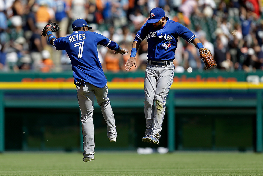 . Toronto Blue Jays\' Jose Reyes (7) and Jose Bautista celebrate after their 7-3 win against the Detroit Tigers in a baseball game in Detroit, Thursday, June 5, 2014. (AP Photo/Paul Sancya)