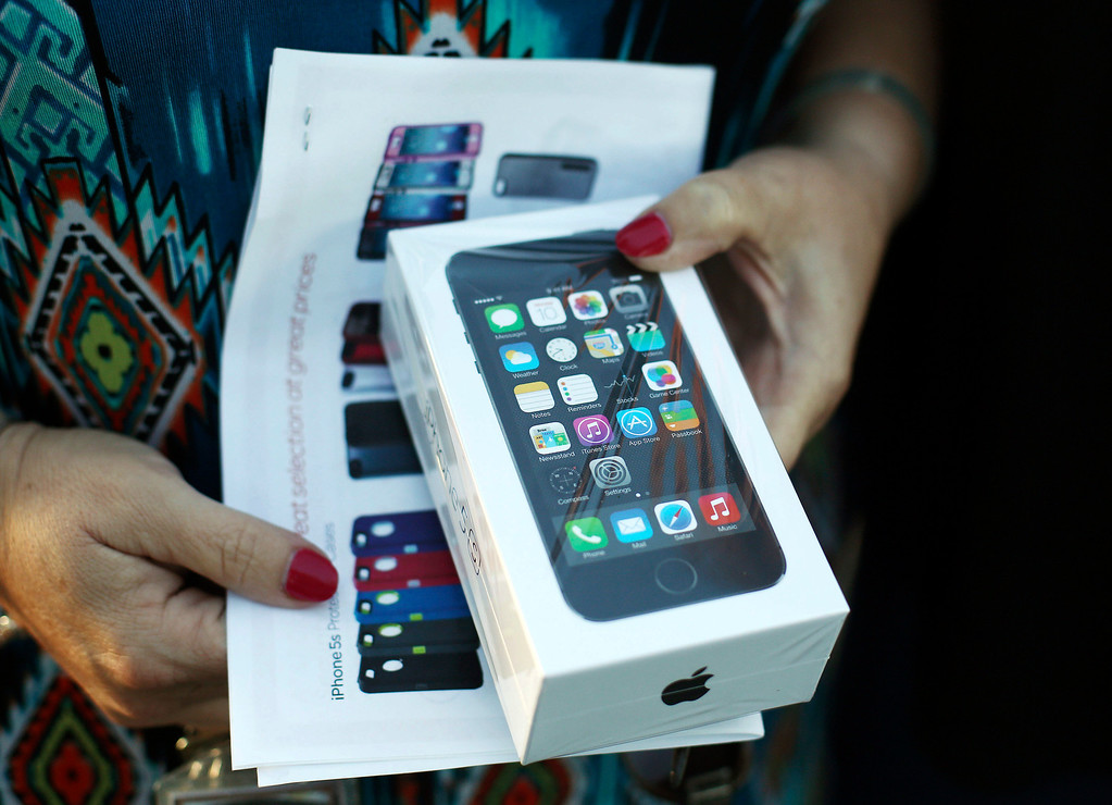 . JoAnn Dulaney displays a new iPhone 5s sold in Pembroke Pines, Fla., Friday, Sept. 20, 2013. Dulaney stood in line for 13 hours to buy the phone for her son. (AP Photo/J Pat Carter)