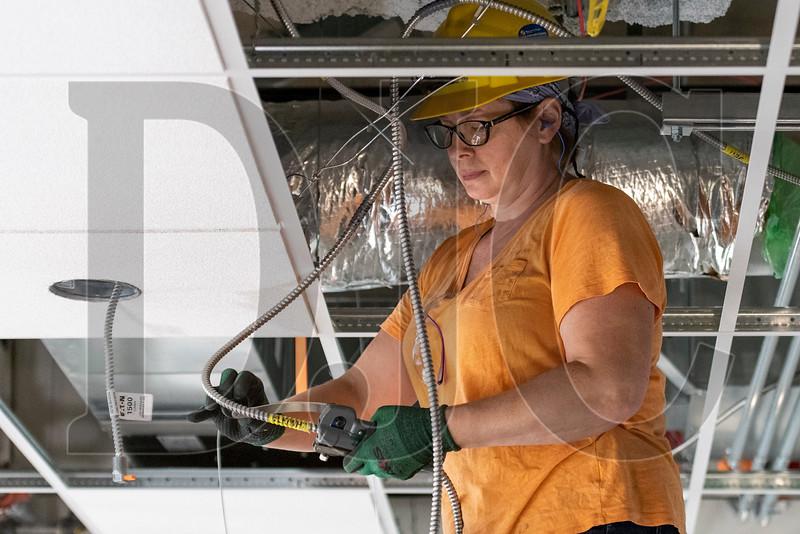 Debbra Glaubitz, a journeyman electrician with Local 48 and Oregon Electric Group, installs conduit in a ceiling grid at Wells Fargo Center. (Josh Kulla/DJC)