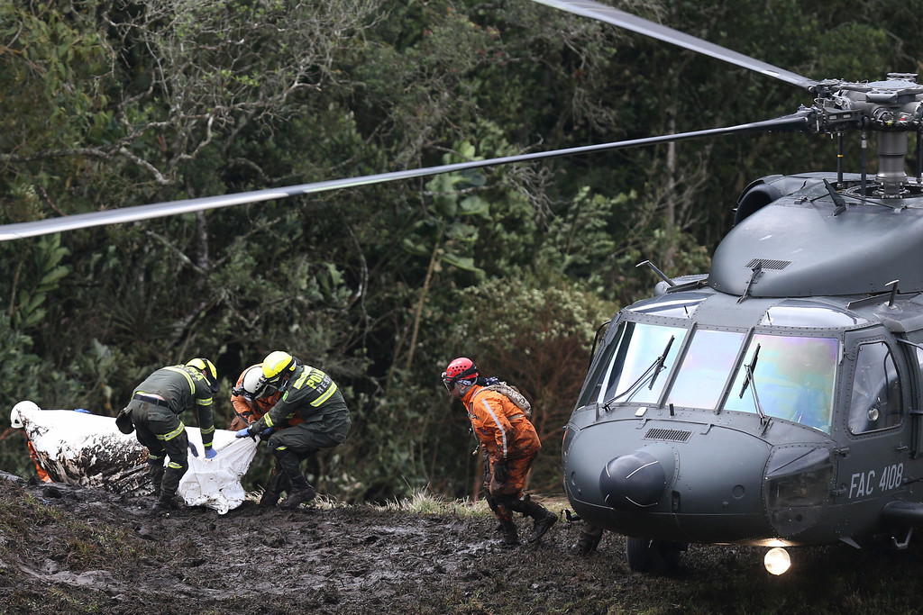 . Rescue workers move the body of a victim of an airplane crash towards a waiting helicopter, in La Union, near Medellin, Colombia, Tuesday, Nov. 29, 2016. The chartered plane was carrying a Brazilian soccer team to the biggest match of its history when it crashed into a Colombian hillside and broke into pieces, killing 75 people and leaving six survivors, Colombian officials said Tuesday. (AP Photo/Fernando Vergara)