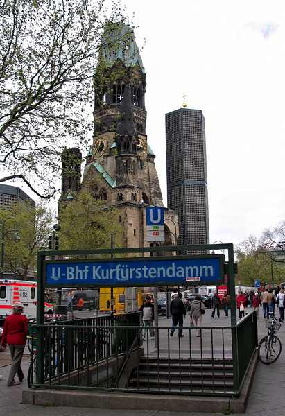 Kurfurstendamm U-Bahn station with Kaiser Wilhelm churches old and new in the background. The old church is a ruin, thanks to WW2. Sadly, the new one still stands.